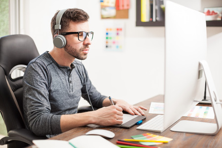 Portret van een Latijns-Hispanic freelance designer dragen van een bril en het luisteren naar muziek met een hoofdtelefoon op het kantoor