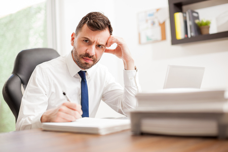miserable: Portrait of an unhappy businessman going to a pile of papers to sign and looking angry and miserable