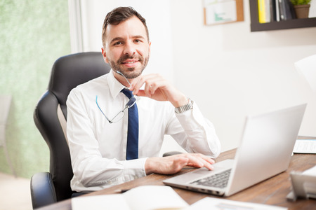 eyestrain: Good looking young Latin businessman working on a laptop computer in his office while holding a pair of glasses in his hand