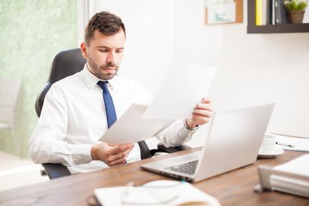 revisando documentos: Ocupado joven empresario con una barba revisar algunos gráficos de rendimiento en su oficina Foto de archivo
