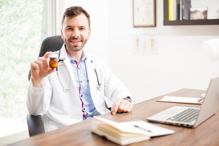 recommending: Portrait of a happy attractive young doctor in a lab coat holding a bottle of pills and recommending their use Stock Photo