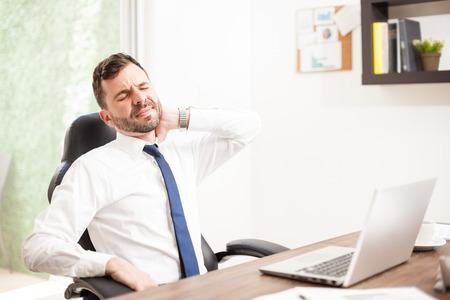 Portrait eines jungen Anwalt mit einem Bart leidet Nackenschmerzen im Büro aufgrund einer schlechten Sitzhaltung