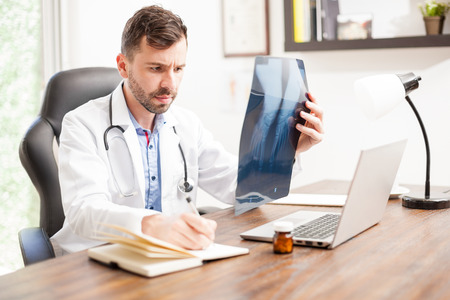 computer desk: Portrait of a good looking young orthopedist with a beard working in his office and taking notes from some x-rays