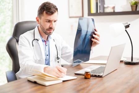 pies masculinos: Retrato de un buen ortopedista joven que busca con una barba que trabaja en su oficina y tomando notas de algunas radiografías