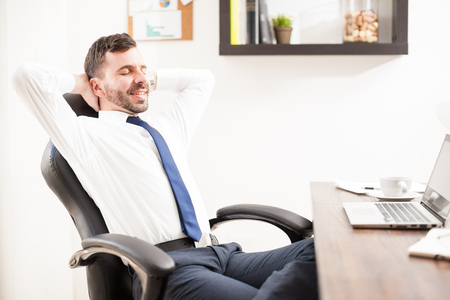 leaning: Profile view of a young businessman leaning back on his chair and relaxing from work at his office Stock Photo