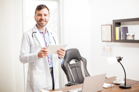 Friendly and attractive young physician looking at some patients history on a tablet computer while standing in his office