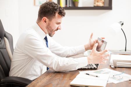 enfado: Vista de perfil de un businssman fuus gritando a su ordenador portátil en la frustración por su mal funcionamiento