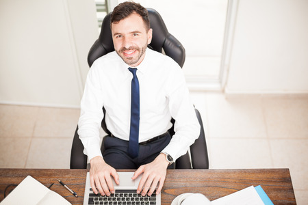 High angle view of a good looking Hispanic businessman working on a laptop computer in his office and smiling