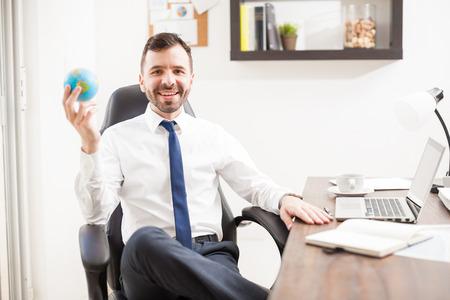 Feliz joven hombre de negocios hispanos con un pequeño globo en la mano como símbolo de su compañía convertirse en mundial