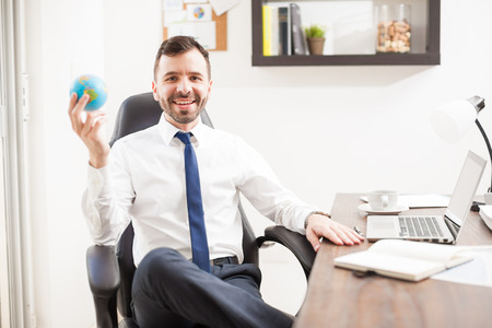 companies: Happy Hispanic young businessman holding a small globe in his hand as a symbol of his company becoming global