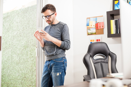 break from work: Portrait of a good looking young designer taking a break from work to use his smartphone at the office Stock Photo