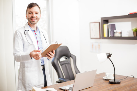 Portrait of a friendly Hispanic young doctor welcoming his patients in his office and holding a chart with medical history