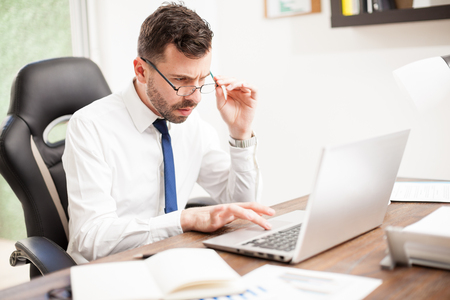 businessman working at his computer: Portrait of a young businessman with eye fatigue looking over his glasses while working on a laptop computer in an office Stock Photo