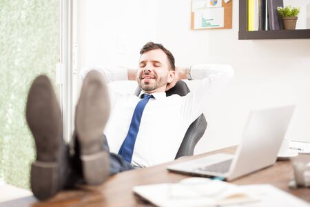 feet up: Happy businessman with his feet up the desk and leaning on his chair taking a break from work and relaxing