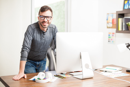Portrait of a young Hispanic graphic designer leaning on his office desk and looking confident with a smile