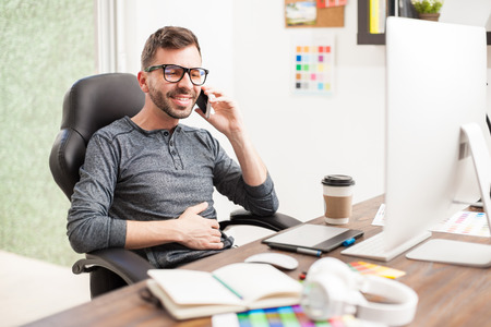 home office: Portrait of a good looking Hispanic young man talking on a smartphone while sitting in a home office