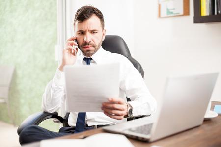 abogado: Retrato de un abogado seriosu muy revisando algunos documentos legales sobre el teléfono en su oficina