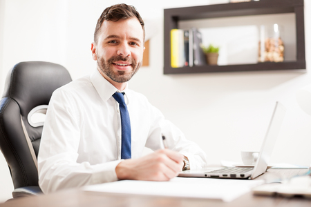 busy beard: Young Hispanic businessman signing a few documents and taking some notes in his office and smiling