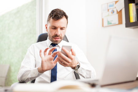 busy beard: Young man reading emails and doing business with his clients using a smartphone in his office