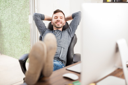 working desk: Portrait of a happy young man relaxing in his office after finishing all his work for the day