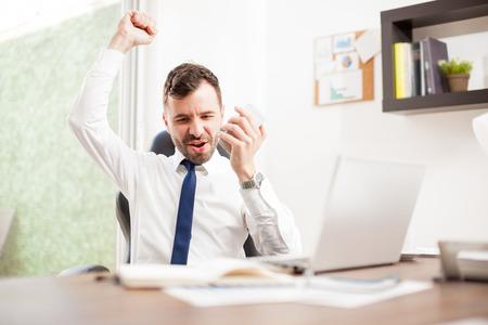 Aufgeregter junger Geschäftsmann feiert und seinen Arm erhöhen, nachdem einige große Nachrichten über das Telefon in seinem Büro zu hören Standard-Bild