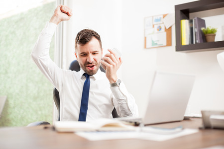 uomo felice: Excited young businessman celebrating and raising his arm after hearing some great news over the phone in his office