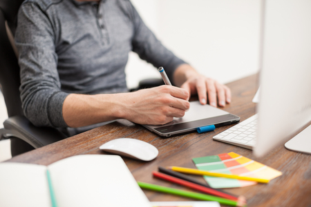 creative artist: Closeup of a male graphic designer using a pen tablet to do some design work at his office Stock Photo