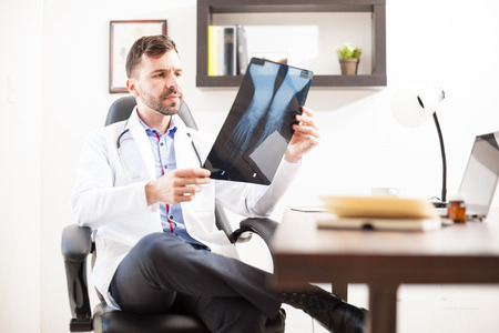 orthopedist: Handsome Hispanic orthopedist sitting in an office and looking at some feet x-rays from a patient Stock Photo
