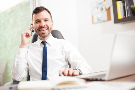 telemarketer: Portrait of a happy Hispanic telemarketer wearing a headset and smiling to customers while sitting at an office Stock Photo