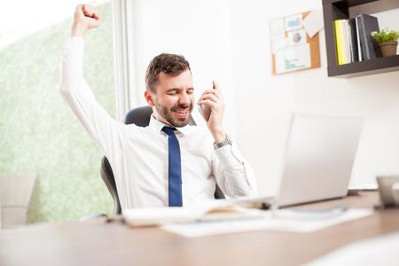 Retrato de un hombre de negocios hispanos feliz levantando el brazo y la celebración que acaba de recibir un gran nuevo proyecto a través del teléfono Foto de archivo