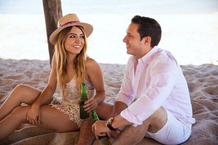 mooie vrouwen: Mooie jonge vrouw die met een man flirt terwijl ze beiden bier drinken en hun bedrijf op het strand genieten