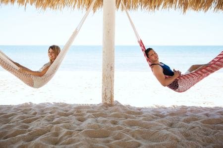 luna de miel: pareja joven linda que pone en hamacas y disfrutar de sus vacaciones de luna de miel en la playa Foto de archivo