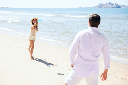 flying disc: Young woman throwing a flying disc to her boyfriend and having fun together at the beach during their summer vacation Stock Photo