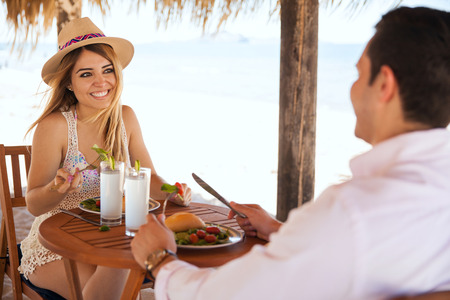 romantic beach: Point of view of a young man having lunch with his girlfriend during a romantic date at the beach Stock Photo
