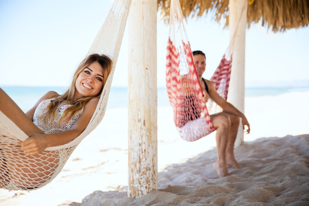 eye shade: Happy young Hispanic woman relaxing in a hammock with her husband while enjoying their honeymoon at the beach Stock Photo