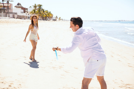 flying disc: Good looking young couple having a fun date at the beach and playing with a flying disc together