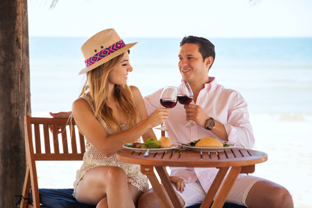 resort beach: Attractive young couple making a toast and celebrating their anniversary with wine and a meal at the beach Stock Photo