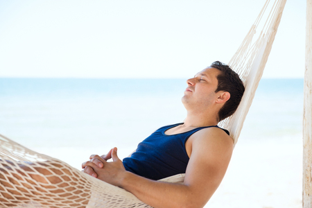 Profile view of a handsome young man taking a nap and sleeping in a hammock at the beach Reklamní fotografie