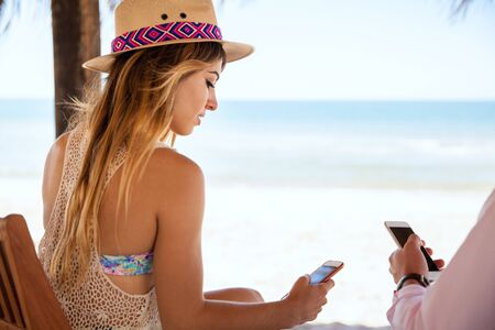 20s  closeup: Pretty young brunette using her smartphone while ignoring her boyfriend during their vacation at the beach
