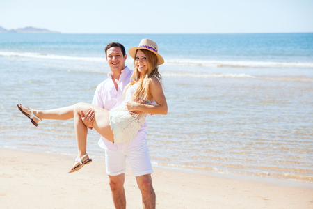 young wife: Portrait of a young couple of Hispanic newlyweds hanging out at the beach and the guy carrying his wife