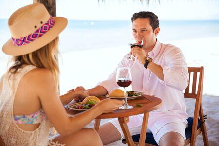 tomando vino: Apuesto joven de beber un poco de vino y comer el almuerzo con su novia mientras estaba de vacaciones en la playa Foto de archivo
