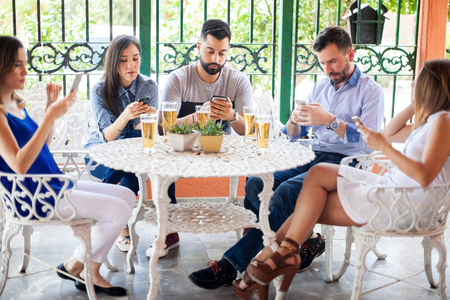 Group of young Latin friends ignoring each other and looking at their smartphones during a reunion in a backyard Stock Photo - 60089794