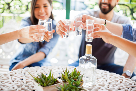 Closeup of a group of young Hispanic friends having fun together and drinking shots of tequila during a barbecue Zdjęcie Seryjne - 60089795