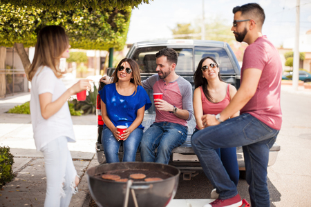 good looking: Group of good looking young friends having a good time while drinking beer and  grilling burgers Stock Photo