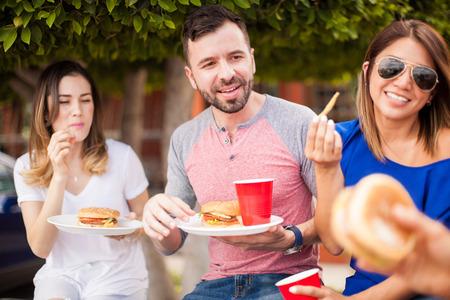 Knappe Spaanse jonge man die hamburgers en frietjes met een aantal van zijn vrienden bij een barbecue eet en wat leuks heeft