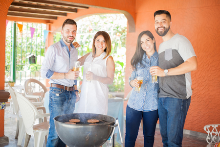 couples outdoors: Two young Latin couples spending time together and cooking some burgers while drinking beer outdoors Stock Photo