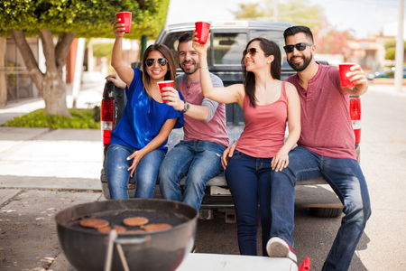 four friends: Four Latin friends laughing and having fun while grilling burgers at a barbecue and drinking some beer