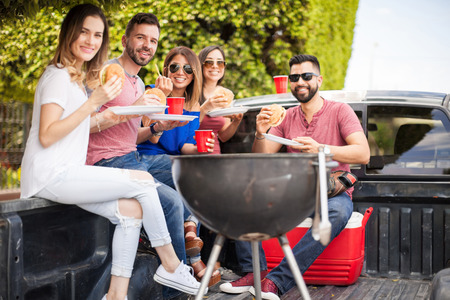 eye contact: Attractive young people drinking beer and eating burgers next to a grill outdoors and making eye contact