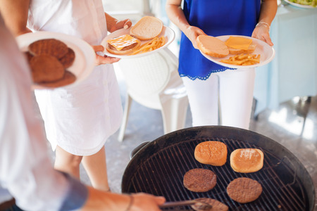 Closeup of some friends waiting in line next to the grill to get served some food during a barbecue in a patio
