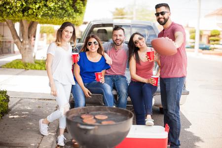 Groep van goed uitziende vrienden en voetbal fands grillen hamburgers en bier drinken terwijl Bumperkleven op een zondag spel